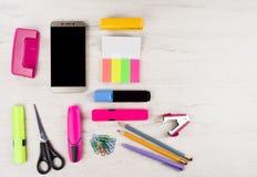 Uno smartphone e una varia cancelleria fotografie stock libere da diritti