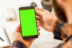 Uno smartphone nero con lo schermo verde per la mano compositing chiave di intensità che tiene smartphone nero con lo schermo ver immagini stock