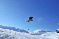 Uno snow-boarder che realizza corsa con gli sci aerea immagine stock