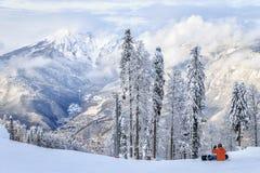 Uno snowboarder che si siede sul pendio di montagna nevoso di inverno della stazione sciistica di Soci Bello paesaggio scenico immagine stock libera da diritti