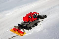 Uno spazzaneve rosso sulla montagna della neve Fotografia Stock Libera da Diritti