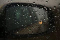 Uno specchio di automobile attraverso la finestra ha gocciolato con pioggia Fotografie Stock