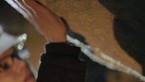 uno speleologo che esplora la parete calcarea del ` s della caverna 4K video d archivio