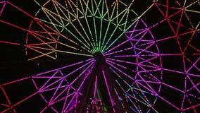 Uno spettacolo di luci variopinto della ruota panoramica al film di sera stock footage