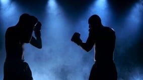 Uno sportivo d'inscatolamento di due giovani in uno studio fumoso in siluetta archivi video