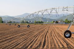 Uno spruzzatore gigante dello spruzzo per irrigare un campo recentemente arato 613 Fotografia Stock Libera da Diritti