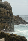 Uno spruzzo di acqua contro le rocce Fotografia Stock Libera da Diritti