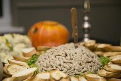 Uno spuntino insolito su un grande piatto, nel centro di cui è una montagna di patè sotto forma di cervelli con un coltello pugna immagine stock libera da diritti