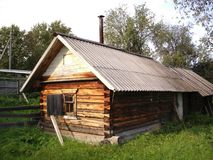 Uno stabilmento balneare russo di legno in un villaggio circondato da erba sulla a fotografia stock