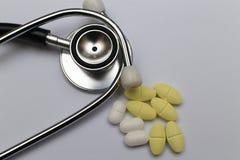 uno stetoscopio e le pillole gialle Immagini Stock
