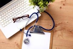 Uno stetoscopio medico vicino ad un computer portatile su un di legno Fotografie Stock