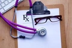 Uno stetoscopio medico vicino ad un computer portatile su un di legno Fotografia Stock