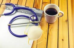 Uno stetoscopio, una lavagna per appunti della cartella di anamnesi, una matita e una tazza di caffè immagine stock