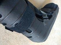 Uno stivale nero, una colata o le calzature ortopedica o medica fotografia stock