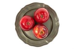 Uno storico, di piastra metallica con tre mele rosse su un fondo bianco Immagini Stock