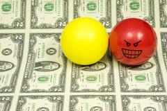 Uno strato di 2 banconote in dollari e palle di sforzo con il attitudee Immagini Stock