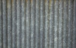 Uno strato ondulato del metallo grigio sporco con le linee verticali della ruggine immagine stock