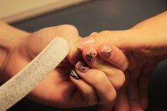 Uno studente ai corsi di formazione di un manicure prepara la mano di un cliente di signora con un archivio prima dell'applicazio Fotografia Stock