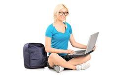 Uno studente biondo sorridente che si siede su un pavimento e che lavora ad un computer portatile Fotografie Stock
