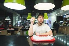 Uno studente che si siede ad un fast food con alimento in sua mano e leccato su Ritratto di un uomo affamato con un hamburger Fotografia Stock