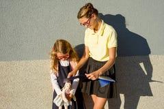 Uno studente della High School aiuta uno studente della scuola elementare ad imparare la t immagine stock