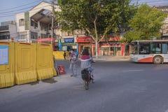 Uno studente della 'junior high school'della bici Sta attraversando una strada della costruzione Fotografia Stock