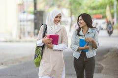 Uno studente di due asiatici che cammina sulla città universitaria Fotografia Stock