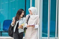 Uno studente di due asiatici che cammina sulla città universitaria Immagini Stock