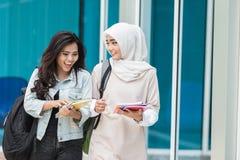 Uno studente di due asiatici che cammina sulla città universitaria Fotografie Stock