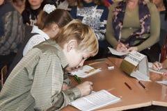 Uno studente minore sconosciuto ad uno scrittorio scrive qualcosa in un notebo Fotografie Stock Libere da Diritti