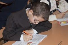 Uno studente minore sconosciuto ad uno scrittorio scrive qualcosa in un notebo Immagini Stock Libere da Diritti