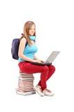 Uno studente sorridente con lo zaino che scrive su un computer portatile e su una o di seduta Immagine Stock Libera da Diritti