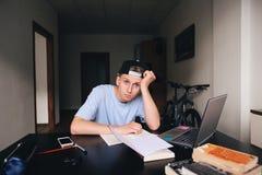 Uno studente stanco che si siede al suo scrittorio nella sua stanza lavoro Uno sguardo alla macchina fotografica Fotografie Stock Libere da Diritti