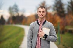Uno studente sveglio annota i suoi pensieri in suo taccuino facendo uso di una matita Il tipo sta tenendo un taccuino in sue mani fotografia stock