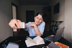 Uno studente teenager sorridente che fa selfie mentre studiando a casa dietro uno scrittorio nella stanza Tasse di Selfies Fotografie Stock