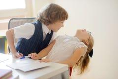 Uno studente, un ragazzo e una ragazza di due giovani sedentesi ad uno scrittorio della scuola Fotografie Stock Libere da Diritti