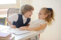 Uno studente, un ragazzo e una ragazza di due giovani sedentesi ad uno scrittorio della scuola Immagine Stock Libera da Diritti