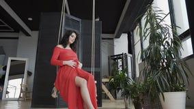 In uno studio alla moda vicino ad un fiore verde, una donna incinta si siede sull'oscillazione e delicatamente segna il suo stoma archivi video