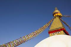 Uno Stupa buddista tibetano Boudhanath con gli occhi e le bandiere multicolori di preghiera contro un cielo blu pulito fotografia stock libera da diritti