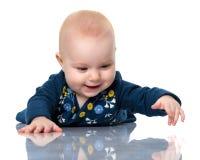 Uno sveglio, molto bambina sta trovandosi sul pavimento su un backgr bianco immagine stock libera da diritti