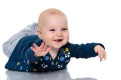 Uno sveglio, molto bambina sta trovandosi sul pavimento su un backgr bianco fotografia stock