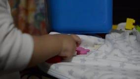 Uno y medio bebé año que pone bloques del lego en compartimiento azul metrajes