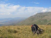 Uno zaino sulla terra con dietro le montagne dell'Albania fotografia stock