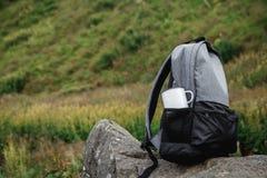 Uno zaino, una tazza, un blocco note e una mappa stanno trovando sull'erba Attrezzatura turistica La mela si trova nella tasca de fotografia stock libera da diritti
