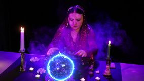 Uno zingaro alla tavola ? impegnato nella magia con una sfera di cristallo che emette le scintille elettriche e le bolle archivi video