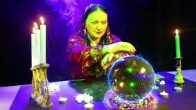 Uno zingaro nel salone magico ? impegnato nella magia con una sfera di cristallo, da cui il segno del fuoco di Bitcoin compare stock footage