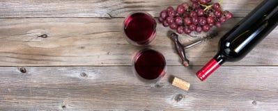 Unopen бутылка красного вина и стекел с виноградинами на деревенской древесине Стоковые Фотографии RF