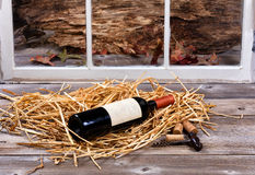 Unopen bottle of red wine on straw with opener Royalty Free Stock Photography