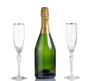 Unopened bottle of champagne and drinking glasses isolated on wh Stock Photography