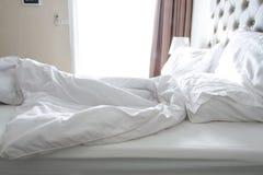 Unordentliche Bettwäscheblätter und -kissen Stockfotos